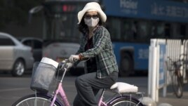 A Chinese woman wearing a face mask on a bicycle waits to cross a street in Beijing, May 31, 2013.