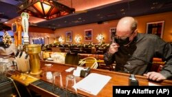 Steve Olsen, the owner of the West Bank Café, reads the specials over the phone to a customer in the empty restaurant. Photo taken on Saturday, Jan. 9, 2021. (AP Photo/Mary Altaffer)