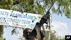 A Somali government soldier stands guard near the Tarbunka frontline in the capital, Mogadishu. Somalia's transitional government and a recently-armed Sufi group have initialed a tentative agreement to fight Islamist extremism and enter a power-sharing ac