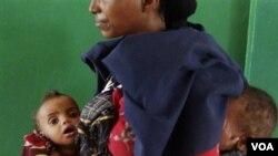 Seorang perempuan Somalia menggendong dua anaknya yang mengalami kurang gizi parah bulan Agustus silam (foto:dok).