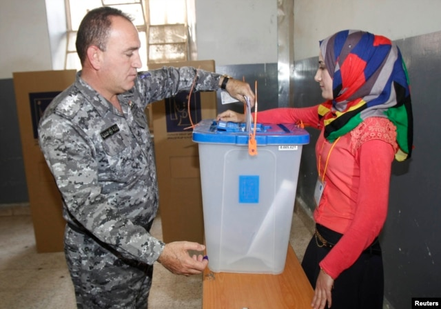 An Iraqi policeman casts his vote into a ballot box during early voting for the parliamentary election in Kirkuk, north of Baghdad, April 28, 2014.