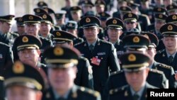 Military delegates from the Chinese People's Liberation Army (PLA) walk towards the Great Hall of the People for a plenary meeting of the National People's Congress (NPC), China's parliament, in Beijing, March 4, 2014.