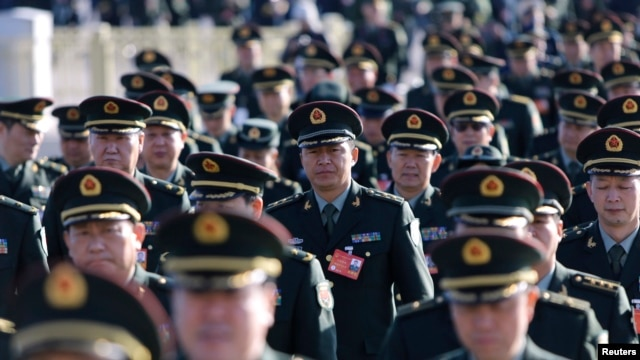 FILE -Military delegates from the Chinese People's Liberation Army (PLA) walk towards the Great Hall of the People for a plenary meeting of the National People's Congress (NPC), China's parliament, in Beijing.