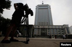 FILE - A television cameraman films the exterior of Jinan Municipality People's Intermediate Courthouse.