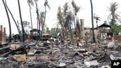 People shift through damaged buildings in Sittwe, capital of Rakhine state, western Burma, June 16, 2012.