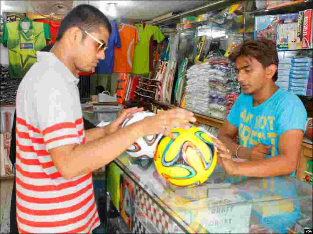 کراچی کی اسپورٹس شاپ پر ایک نوجوان ورلڈ کپ فٹبال کی مشابہت والی گیند خریدنے میں مصروف