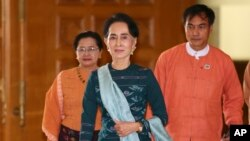 FILE - National League for Democracy party (NLD) leader Aung San Suu Kyi, center, arrives at Myanmar's parliament in Naypyitaw, Myanmar, March 15, 2016.