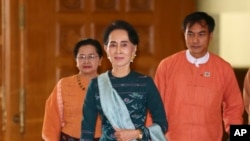 FILE - Myanmar's de facto leader Aung San Suu Kyi, center, arrives at the country's parliament in Naypyitaw, March 15, 2016.