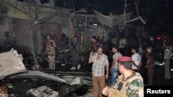 Pasukan keamanan Irak menginspeksi lokasi meledaknya sebuah bom mobil di Nasiriyah (10/8).