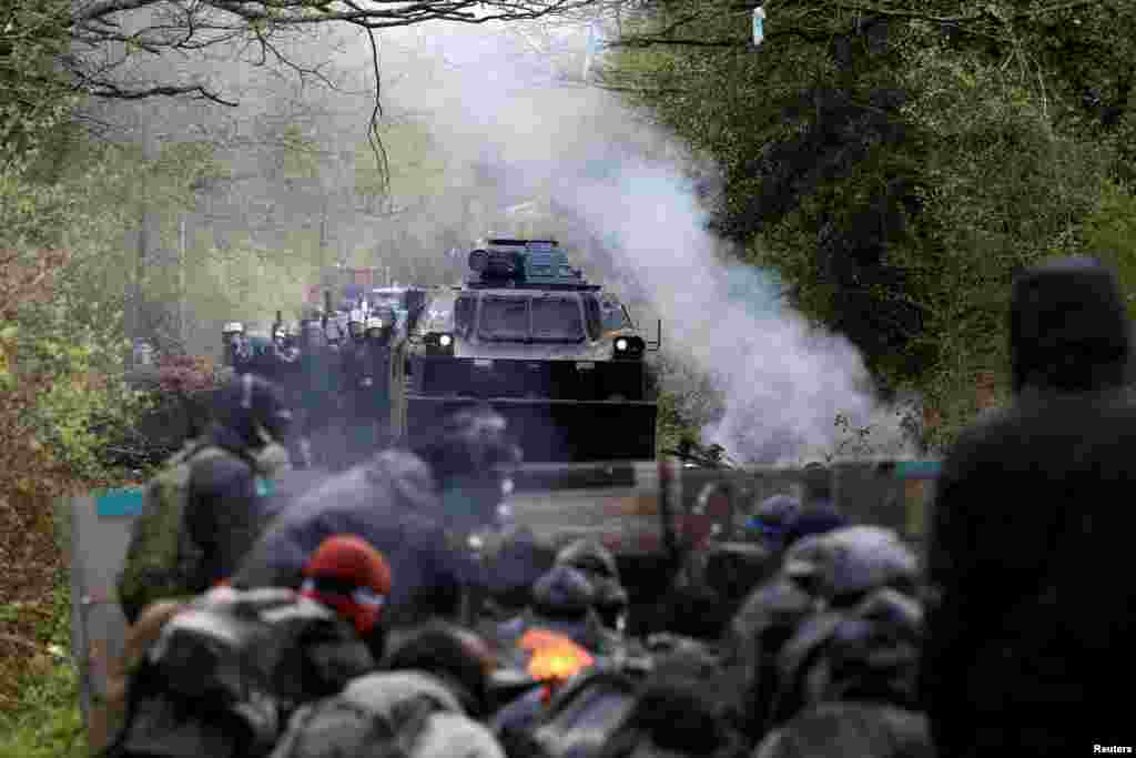 Protesters gather on a road as French gendarmes advance with an armored vehicle during clashes during an evacuation operation in the zoned ZAD (Deferred Development Zone) in Notre-Dame-des-Landes, near Nantes, France.
