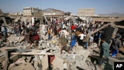 People gather on the rubble of shops destroyed by a Saudi-led airstrike at a market in Sana'a, Yemen, July 20, 2015.