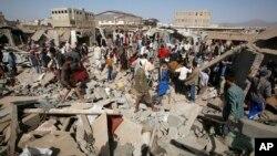 Warga berkumpul di antara reruntuhan bangunan setelah serangan udara Saudi menghancurkan sebuah pasar di Sana'a, Yaman, Senin (20/7).