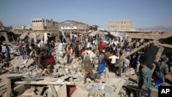 FILE - People gather on the rubble of shops destroyed by a Saudi-led airstrike at a market in Sana'a, Yemen, July 20, 2015.