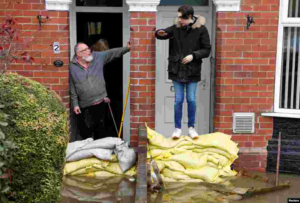 Residents chat by the sandbags at their front doors in a flooded area of Bentley, north of Doncaster, Britain.
