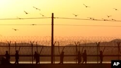 Tentara Korea Selatan berpatroli di dekat pagar kawat berduri dekat perbatasan di desa Panmunjom, Paju (26/3). Korut telah memutuskan jalur komunikasi langsung (hotline) militer degan Korea Utara, menyusul ancaman perang