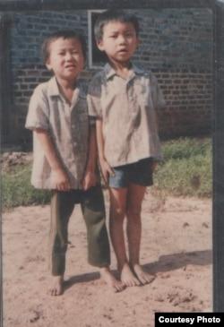 童年的程万里(右)和弟弟在江西老家门口。