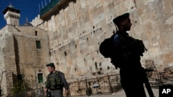 FILE - Israeli border police stand guard on the site known to Jews as the Tomb of the Patriarchs, and to Muslims as the Ibrahimi Mosque, in the West Bank city of Hebron, Jan. 14, 2013.