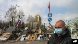 Seorang pria bermasker berdiri di depan barikade dan bendera Rusia dan Soviet di pintu masuk gedung pemerintah di Luhansk, Ukraina (9/4). (AP/Igor Golovniov)