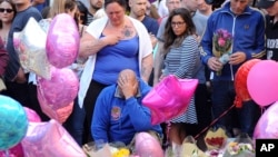 Olivia Campbell's mother, Charlotte Campbell (center) and stepfather, Paul Hodgson (foreground), pay tribute to the victims of the explosion outside Manchester Arena, at St Ann's Square after leading a bikers convoy from their home town of Bury in central Manchester, England, May 25 2017.