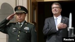 美国国防部长卡特在华盛顿五角大楼接待到访的中国中央军委副主席范长龙(左),两人在乐队演奏两国国歌时敬礼(2015年6月11日, 美国国防部照片)