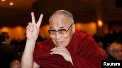 FILE - The Dalai Lama directs a peace sign toward the head table, where U.S. President Barack Obama was seated, during the National Prayer Breakfast in Washington, Feb. 5, 2015.