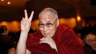 FILE - The Dalai Lama directs a peace sign toward the head table, where U.S. President Barack Obama was seated, during the National Prayer Breakfast in Washington, Feb. 5, 2015.