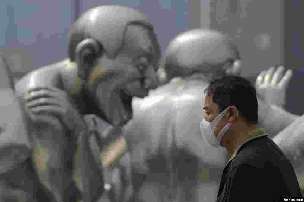 A Chinese man wearing a mask passes by a sculpture during a smoggy day in Beijing.