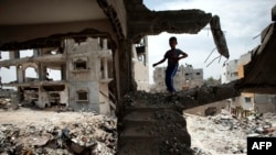 A Palestinian boy plays amid the rubble of his family's former house which was destroyed during the 50-day war between Israel and Hamas militants in the summer of 2014, in the eastern Gaza City Shujaiya neighborhood, May 11, 2015,.