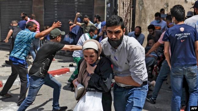 Palestinezët evakuojnë një ndërtesë të goditur nga aviacioni izraelit në Gazë, 11 maj, 2021.