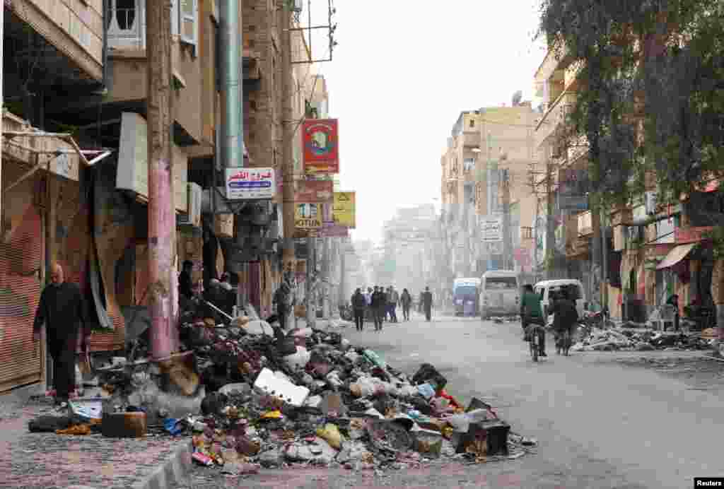 Residents walk past rubbish piled up along a street in Deir al-Zor, Syria, March 13, 2013.