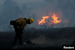A firefighter works to put out hot spots on a fast-moving wind-driven wildfire in Orange, Calif., Oct. 9, 2017.