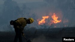 A firefighter works to put out hot spots on a fast-moving wind-driven wildfire in Orange, California, Oct. 9, 2017.
