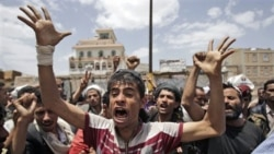 معترضان یمنی در صنعا که خواهان استعفای علی عبدالله صالح هستند توسط سربازان (که در تصویر دیده نمی شوند) از پیش روی به سوی منطقه دولتی بازداشته شده اند - ۸ ژوئن ۲۰۱۱