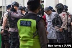 Pemimpin Jemaah Ansharut Daulah (JAD) Zainal Anshori dikawal oleh polisi bersenjata setelah sidang pengadilan di Jakarta pada 31 Juli 2018. (Foto: AFP/Bay Ismoyo)