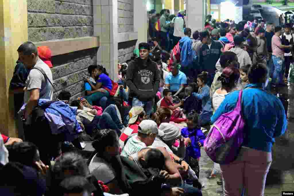 Hondureños esperan para partir con una nueva caravana de migrantes que se dirigirá a Estados Unidos, en una estación de autobuses en San Pedro Sula.