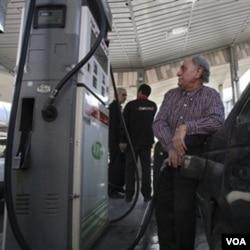 Seorang warga Iran mengisi bensin di sebuah pom bensin di Teheran, Minggu 19 Desember 2010. Harga BBM diperkirakan naik 3-4 kali lipat setelah pemotongan subsidi.