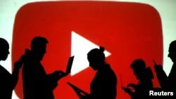 FILE PHOTO: Silhouettes of laptop and mobile device users are seen next to a screen projection of the YouTube logo in this picture illustration taken March 28, 2018.