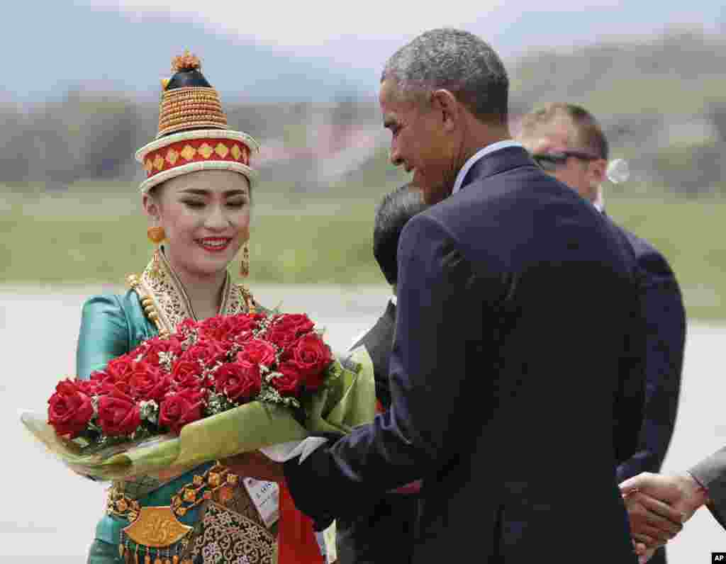 U.S. President Barack Obama receives flowers as he arrives at the Luang Prabang International Airport in Laos, Sept. 7, 2016.