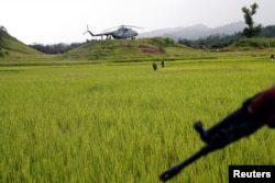 A Myanmar army helicopter transports journalists to an area were government forces found the bodies of Hindu villagers, whom authorities suspect were killed by insurgents last month, in a mass grave near Maungdaw in the north of Myanmar's Rakhine state, Sept. 27, 2107.