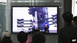 Warga Korea Selatan menyaksikan program televisi di sebuah stasiun kereta api di Seoul, yang menampilkan liputan terkait rencana peluncuran roket Unha-3 Korea Utara, Minggu (8/4).