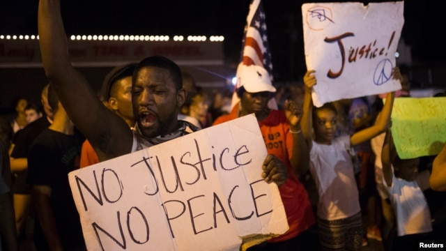 Demonstrators protest the killing of unarmed teen Michael Brown across the street from the Ferguson Police Department  in Ferguson, Missouri, Aug. 23, 2014.