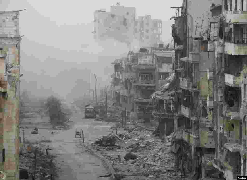 Asap mengepul dari bangunan setelah apa yang disebut para aktivis sebagai pemboman yang dilakukan oleh pasukan setia Presiden Suriah Bashar al-Assad di daerah yang terkepung, Homs, 15 Januari 2014.