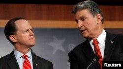 Los senadores Pat Toomey (izquierda) y Joe Manchin informan sobre el acuerdo bipartidista para extender la revisión de antecedentes de los potenciales compradores de armas.