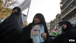 Wanita Iran mengikuti unjuk rasa di depan bekas gedung Kedutaan AS di Teheran dengan membawa poster Ayatollah Khomeini, 4 November 2010.