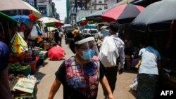 COVID 19 ကူးစက္မႈကို ကာကြယ္ဖို႔ ႏွာေခါင္းစည္းနဲ႔ Face Shield တပ္ထားတဲ့ အမ်ိဳးသမီးတဦးကို ရန္ကုန္ၿမိဳ႕ရွိ ေစ်းတခုမွာေတြ႔ရ။ (ဧၿပီ ၂၁၊ ၂၀၂၀)