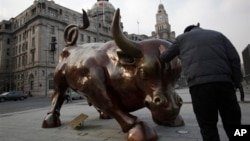 FILE - Man touches statue of a charging bull similar to New York's Wall Street Bull, in Shanghai, China, Feb. 7, 2012.