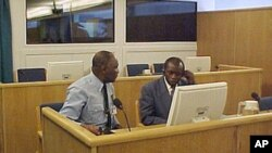 Former Maj. Gen. Augustin Bizimungu, right, commander of the Rwandan armed forces during the 1994 genocide, listens in a courtroom as the indictment on charges of genocide and crimes against humanity is read out against him (File)