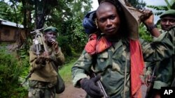 FILE - Congolese government army soldiers carry weapons and mortar equipment on the road to the border town of Bunagana, after their unit returned from the frontline of fighting against rebel forces, in Kinyamahura, Congo.