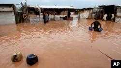 3일 파키스탄 페샤와르 외곽 마을이 홍수로 범람한 가운데, 주민들이 소지품을 건지고 있다.