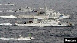 Pesawat pengintai Angkatan Laut China, Haijian No. 66 (tengah) melaju melewati dua kapal penjaga pantai Jepang di sekitar pulau-pulau sengketa di Laut China Timur (foto: dok).